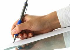 Una mano escribiendo sobre un documento