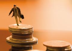Muñeco con maletín sobre montaña de dinero