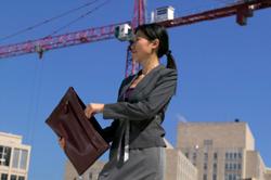 Una mujer en una construcción sacando un plano.