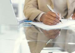 Una persona escribiendo en un documento.