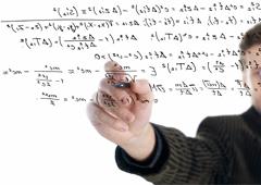 Una pizarra transparente donde se ve a un profesor escribiendo fórmulas en ella