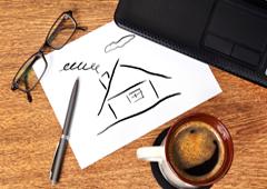 Dibujo de una casita, un boli, unas gafas y un café sobre una mesa