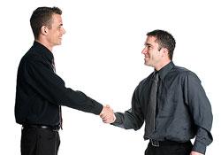 Dos hombres trajeados dándose la mano